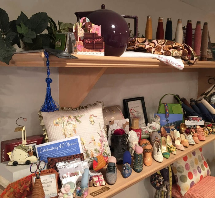Shelves mounted on the wall with sewing themed collectibles on display.