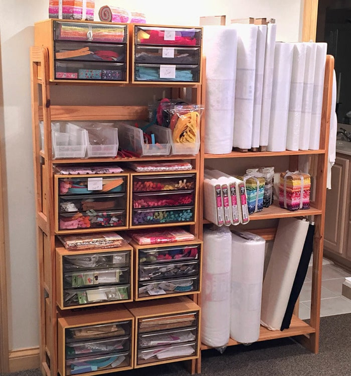 Simple shelves store sewing supplies and bolts of fabric and interfacing.