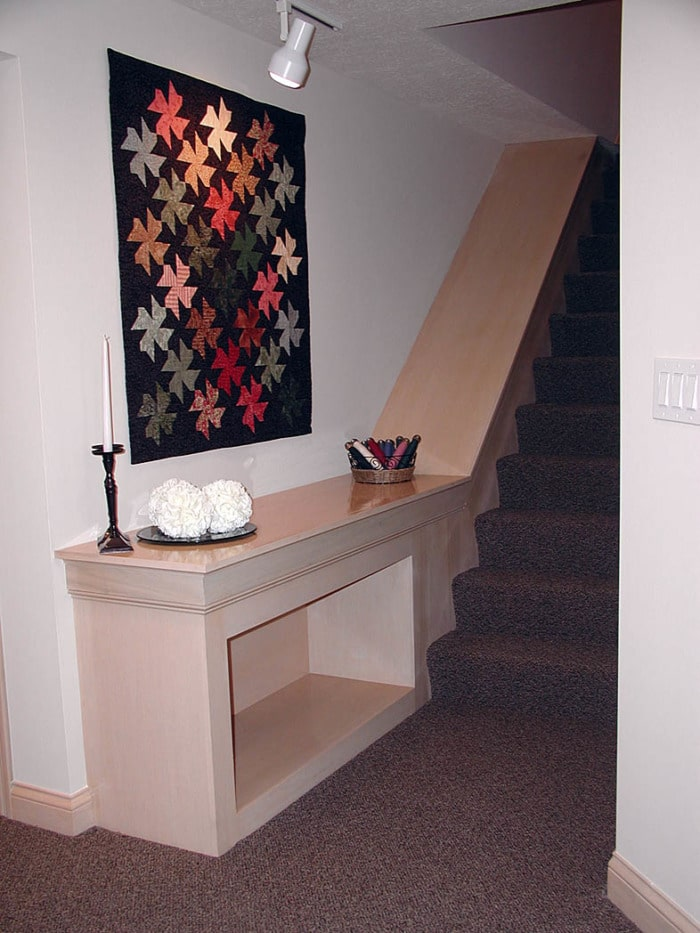 View of staircase with built-in cabinetry to create display space.