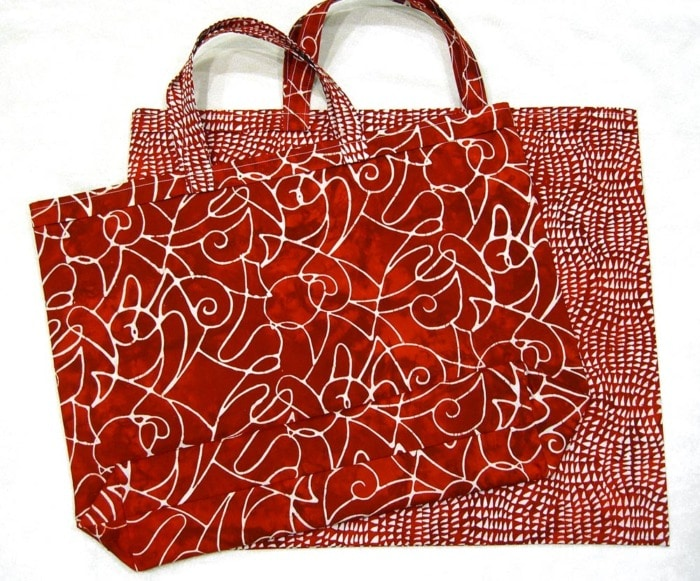 With Two red batik fabric tote bags made from the With Love Tote Bag Free sewing pattern.