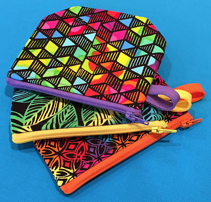Three small zipper pouches in bright fabrics and zippers.