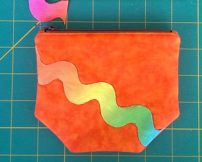 Close up of a small zipper pouch with ricrac sewn to it.