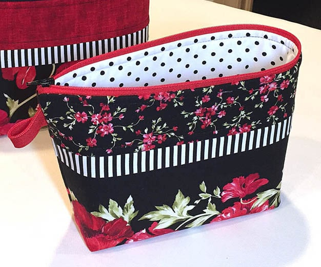 Small zippered pouch made with a border print of florals on a black background.