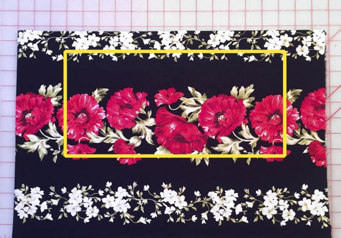 A fabric border print of florals on a black background.