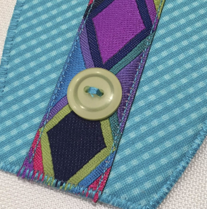 Close up picture of a button sewn in place on top of decorative ribbon on a Button Boats organizer.