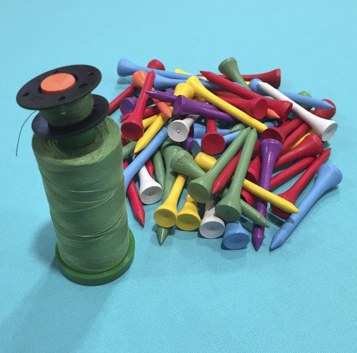 Use golf tees to organize bobbins