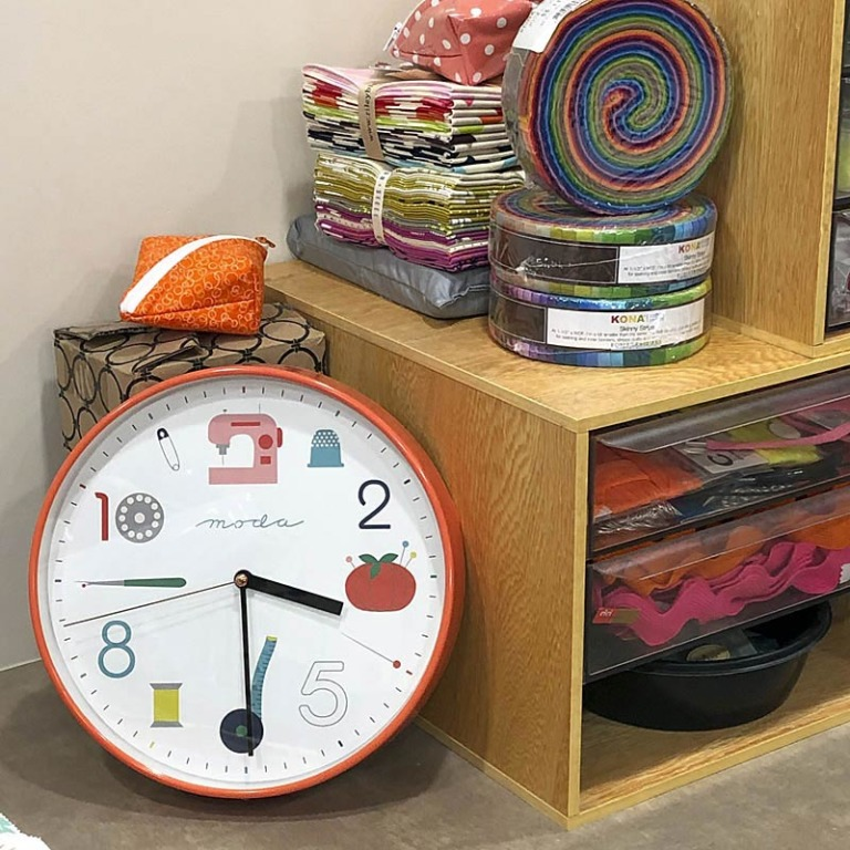Close-up of an orange colored sewing themed wall clock. A clock like this is a perfect sewing gift for stitchy friends