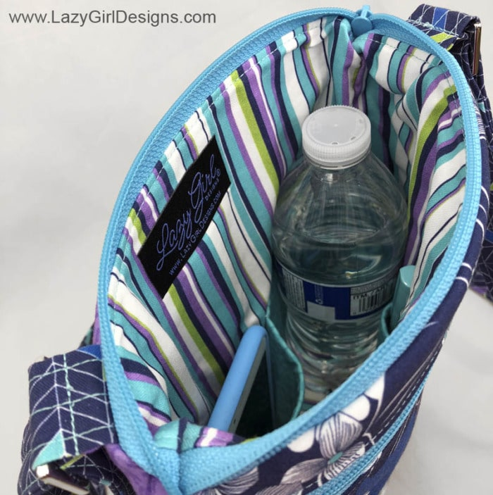 View of inside of cross body bag showing water bottle and cell phone