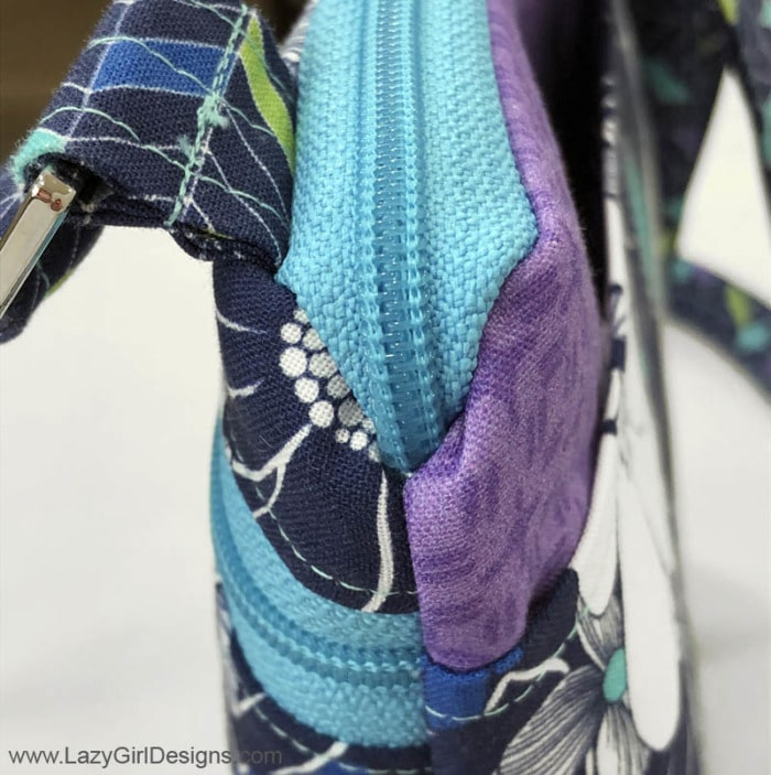 Close-up view of end of zipper on a crossbody bag