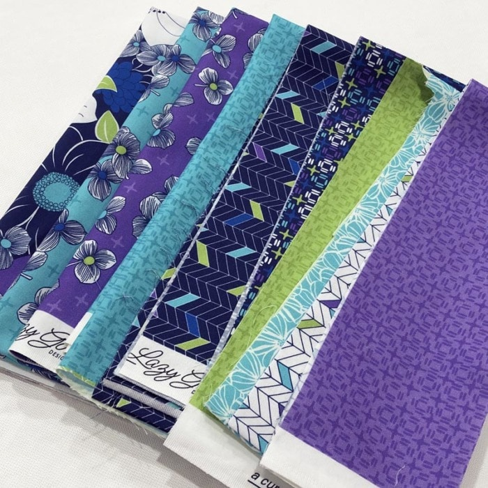 Close up view of sewing tip of how to arrange several fabrics from a single fabric collection in purples, blues, and teals.