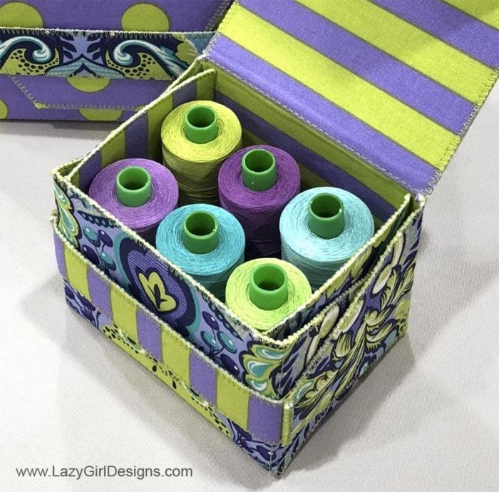 Gift box filled with colorful spools of thread.