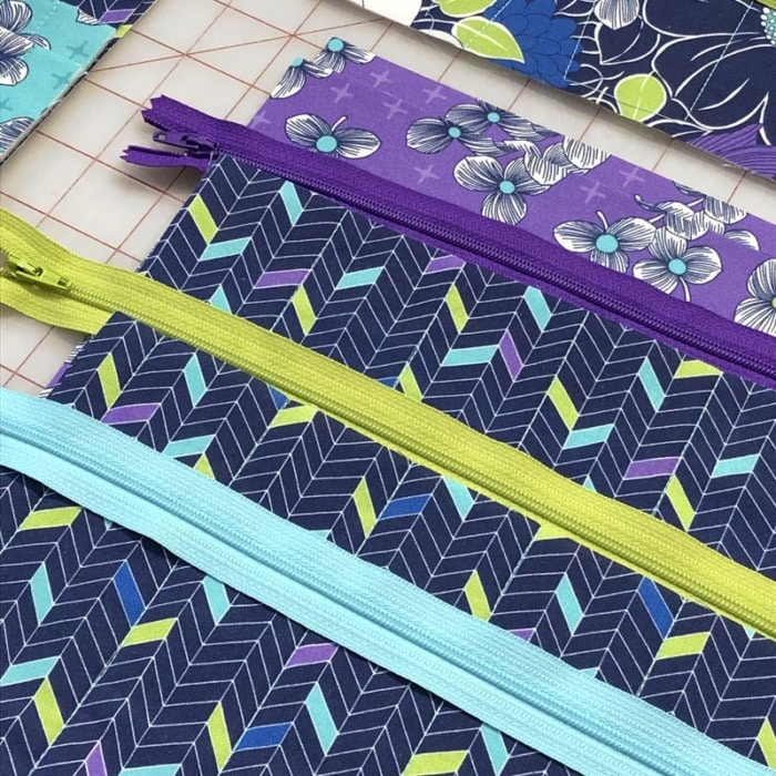 Close up of purple and blue fabric with coordinating zippers.