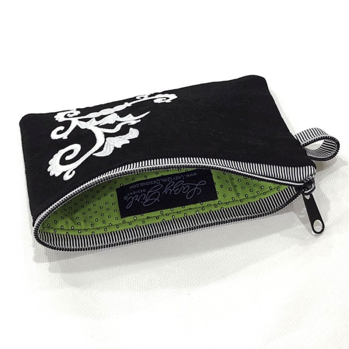 Small zipper pouch unzipped to show the green lining fabric.