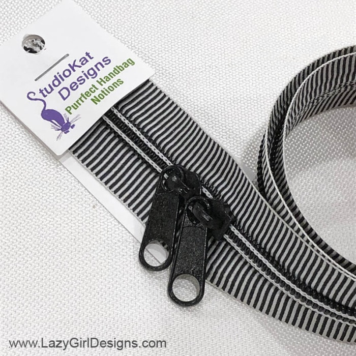 Black and white mini striped zipper with two pulls.