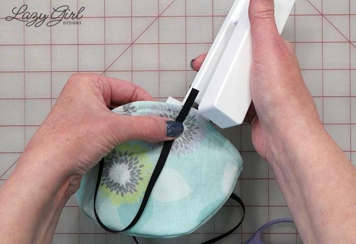 Desk stapler attaching elastic ear loop.