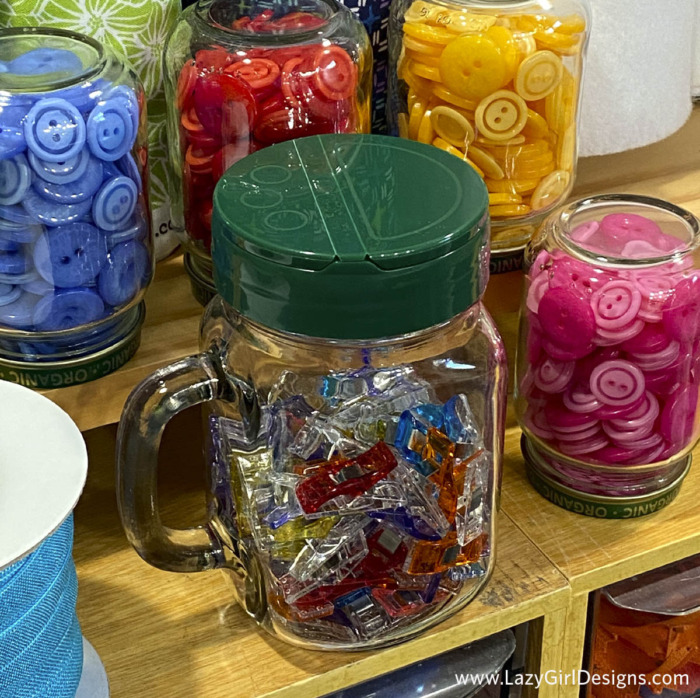 One glass jar filled with sewing clips